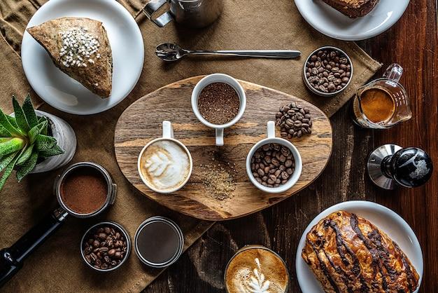 Tiro de ángulo alto de granos de café en frascos en una mesa de desayuno con algunos pasteles Foto gratis