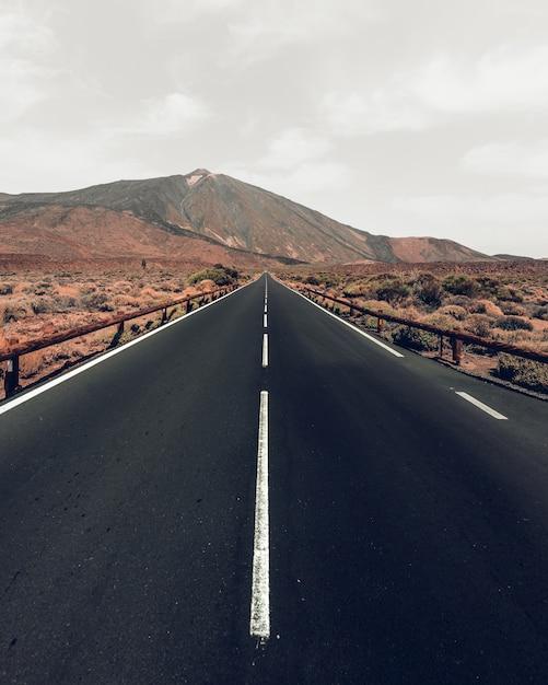 Tiro de ángulo alto vertical de una carretera rodeada de colinas bajo el cielo gris Foto gratis