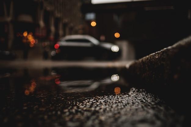 Un tiro de ángulo bajo de un automóvil con reflejo en el charco de agua Foto gratis