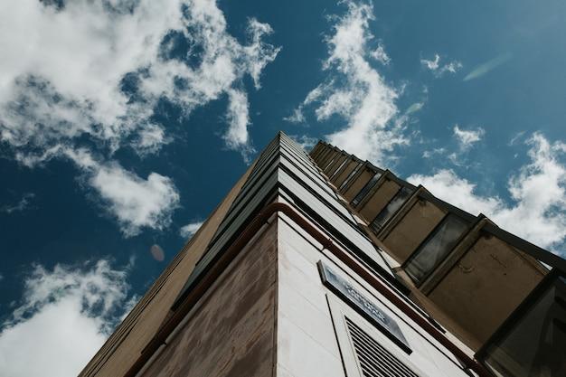 Tiro de ángulo bajo de un edificio alto bajo un cielo azul claro con nubes blancas Foto gratis