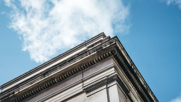 Tiro de ángulo bajo de un edificio arquitectónico bajo un cielo azul claro con nubes blancas Foto gratis