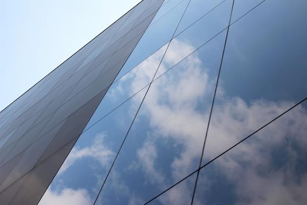 Tiro de ángulo bajo de un edificio comercial de vidrio de gran altura con un reflejo de las nubes y el cielo Foto gratis