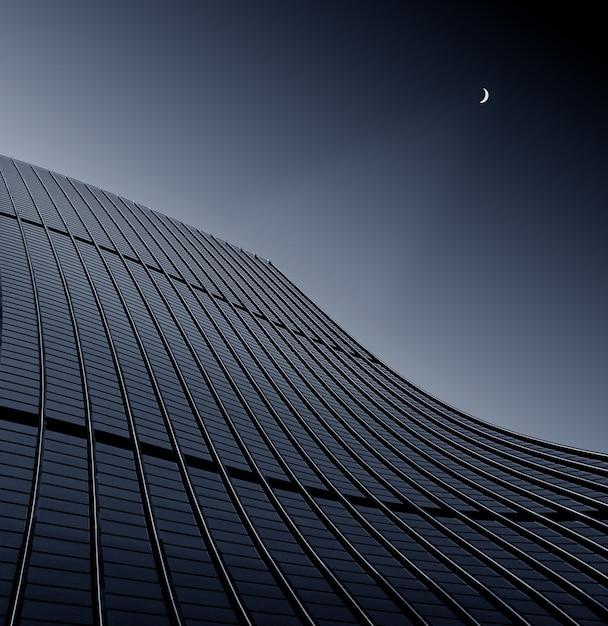 Tiro de ángulo bajo de un edificio empresarial moderno tocando el cielo despejado Foto gratis