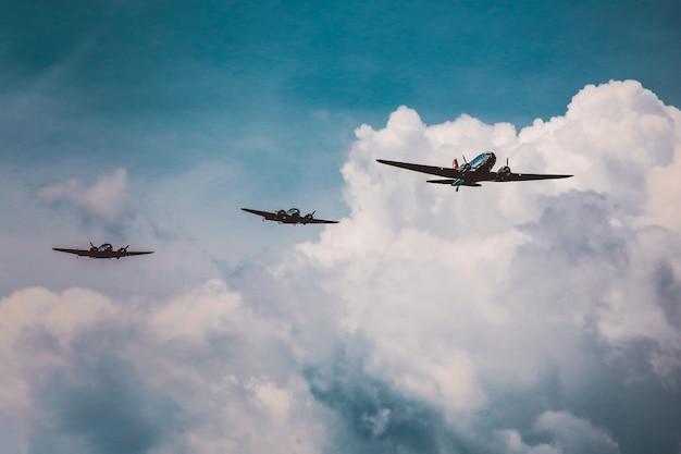 Tiro de ángulo bajo de una gama de aviones preparando un espectáculo aéreo bajo el impresionante cielo nublado Foto gratis