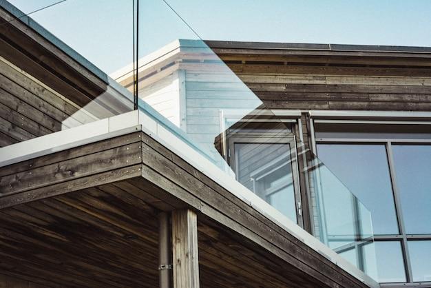 Tiro de ángulo bajo de una moderna casa de madera con bordes de terraza de vidrio Foto gratis