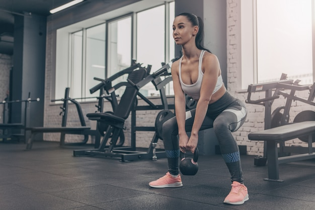 Tiro de ángulo bajo de una sexy atleta femenina haciendo ejercicio con pesas rusas en el gimnasio Foto Premium