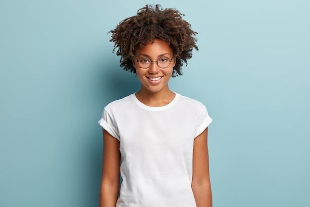 Tiro de cintura para arriba de mujer rizada feliz con sonrisa dentuda, lleva gafas ópticas y camiseta blanca sólida casual, expresa buenas emociones, disfruta de un buen día, aislado sobre fondo azul. expresiones de la cara Foto gratis