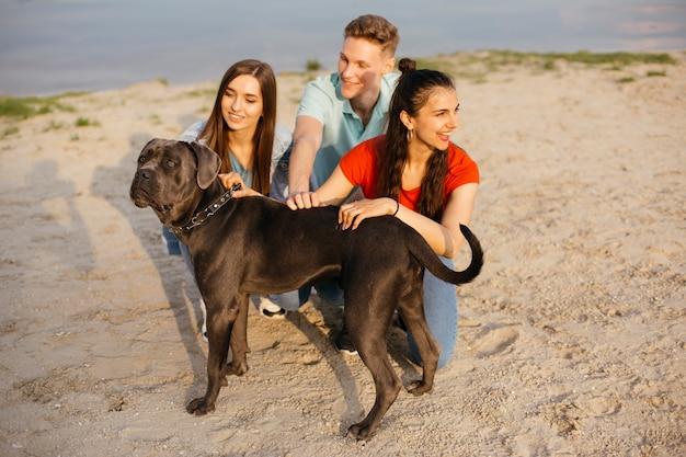Tiro completo amigos con perro en la playa Foto gratis