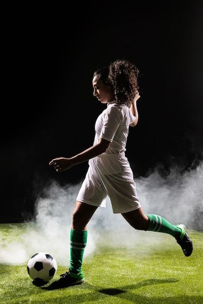 Tiro completo fit mujer jugando al fútbol Foto gratis
