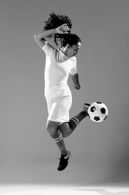 Tiro completo fit mujer jugando con balón de fútbol Foto gratis