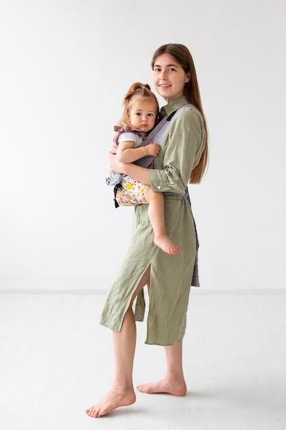 Tiro completo madre y niña posando Foto gratis