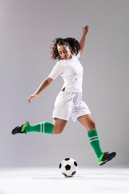 Tiro completo mujer adulta jugando al fútbol Foto gratis