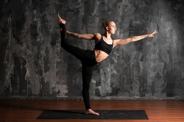 Tiro completo mujer haciendo yoga con fondo de estuco Foto gratis