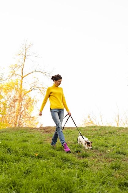 Tiro completo mujer paseando a su perro en el parque Foto gratis