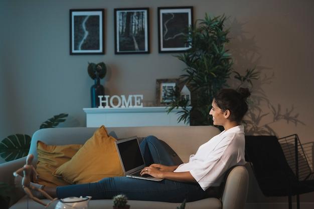 Tiro completo mujer que trabaja en la computadora portátil en casa Foto gratis