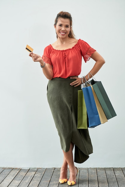 Tiro completo retrato de mujer feliz con bolsas de compras con una tarjeta de crédito al aire libre Foto gratis