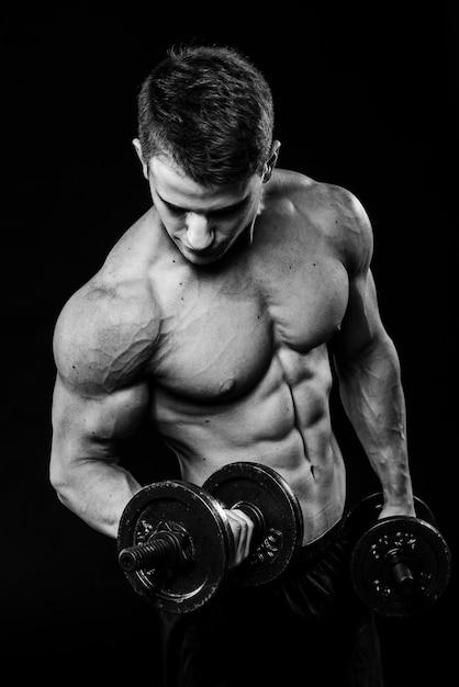 Tiro de contraste blanco y negro oscuro del brazo de estómago de hombre joven fitness muscular. trabajando con pesas aisladas Foto Premium