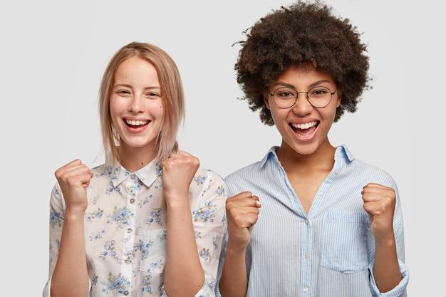 Tiro horizontal de mujeres de raza mixta felices aprietan los puños con felicidad, satisfechos con el resultado del juego, gritan por su equipo favorito, tienen expresiones alegres, aisladas en la pared blanca Foto gratis