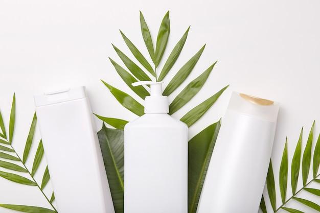 Tiro horizontal de productos cosméticos contra vegetación u hojas. Foto gratis