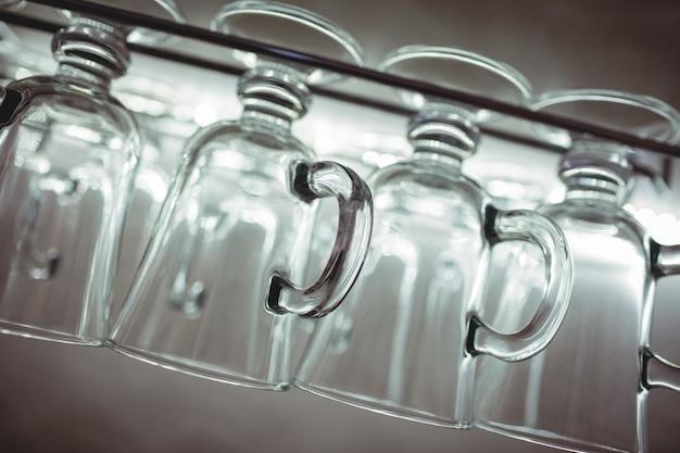 Tiro inclinable de tazas de pinta en el estante en el bar Foto Premium