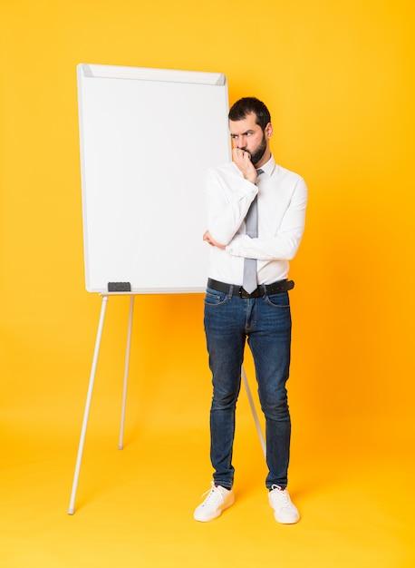 Tiro integral del empresario dando una presentación en el pizarrón sobre amarillo aislado que tiene dudas Foto Premium
