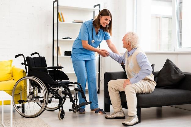 Tiro largo enfermera ayudando a anciano a levantarse Foto gratis