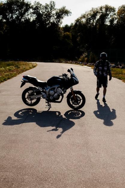 Tiro largo hombre y moto Foto gratis