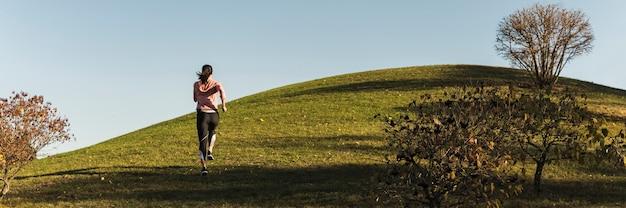 Tiro largo mujer corriendo en el parque Foto gratis