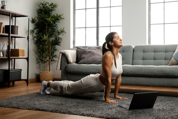 Tiro largo de mujer practicando yoga Foto gratis