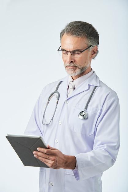 Tiro de longitud media del médico de mediana edad que trabaja con tableta digital Foto gratis