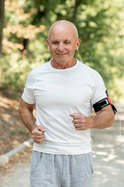 Tiro medio anciano corriendo escuchando música Foto gratis