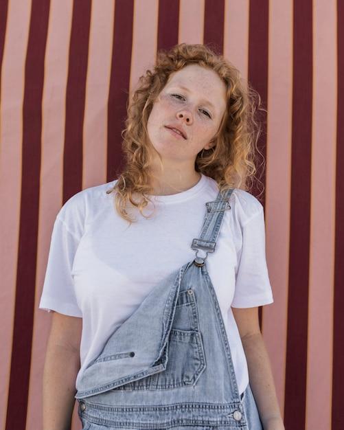 Tiro medio chica seria posando con fondo rayado Foto gratis