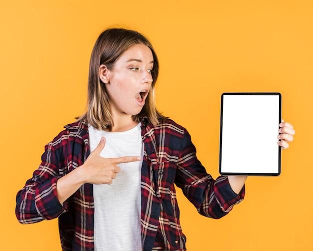 Tiro medio chica sorprendida apuntando a una tableta Foto gratis