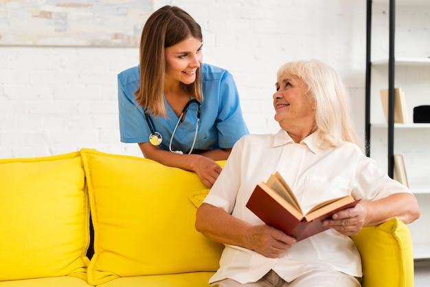 Tiro medio enfermera hablando con anciana Foto gratis