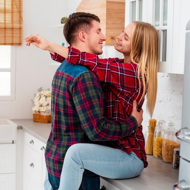 Tiro medio feliz mujer sentada en la encimera de la cocina Foto gratis