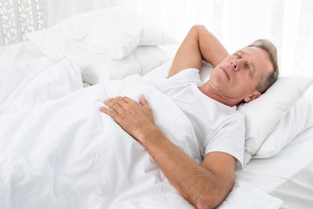 Tiro medio hombre durmiendo con una manta blanca Foto gratis