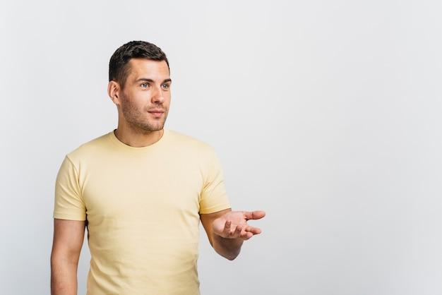 Tiro medio hombre presentando algo con espacio de copia Foto gratis