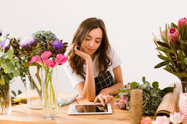 Tiro medio joven florista con tableta Foto gratis