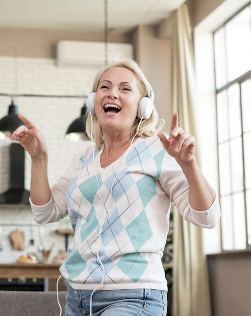 Tiro medio mujer divirtiéndose con auriculares Foto gratis
