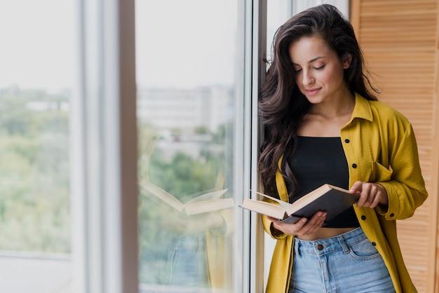 Tiro medio mujer leyendo cerca de la ventana Foto gratis