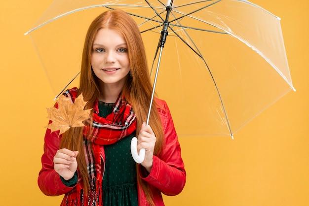Tiro medio mujer con paraguas y hojas Foto gratis