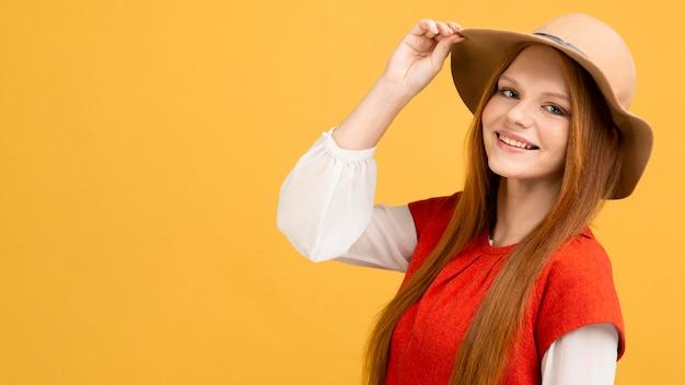 Tiro medio mujer sonriente con sombrero Foto gratis