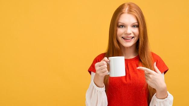 Tiro medio mujer sonriente sosteniendo la taza Foto gratis