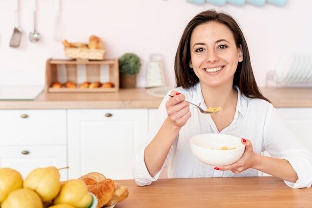 Tiro medio niña sonriente comiendo cereales Foto gratis
