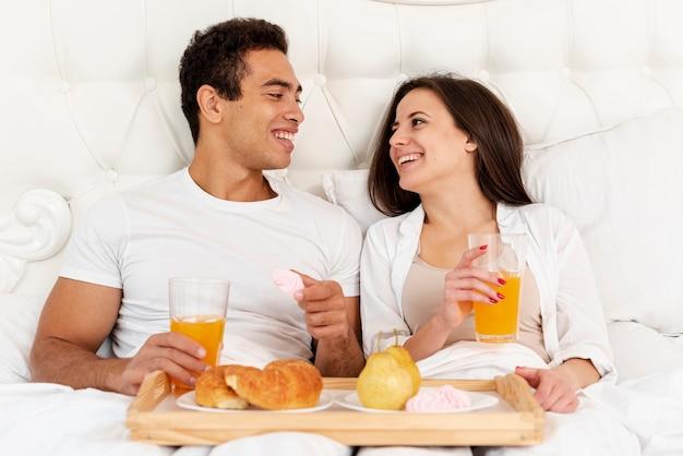 Tiro medio pareja desayunando en la cama Foto gratis