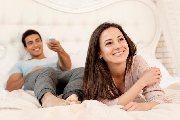 Tiro medio pareja sonriente en el dormitorio Foto gratis