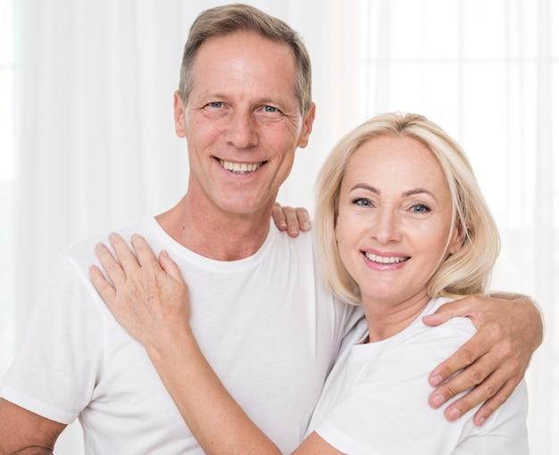 Tiro medio pareja sonriente posando juntos Foto gratis