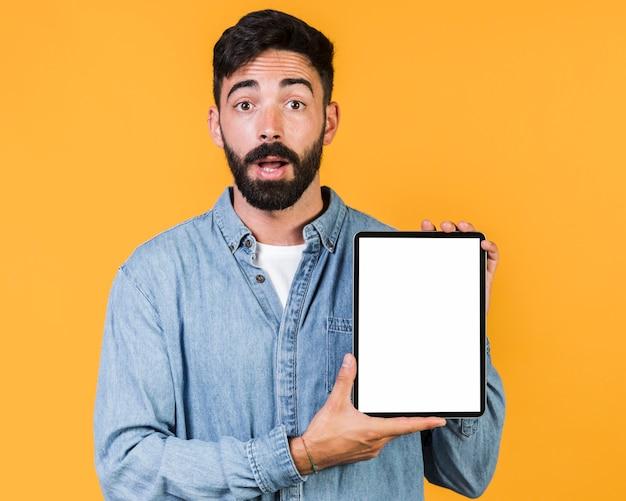 Tiro medio sorprendido chico sosteniendo una tableta Foto gratis