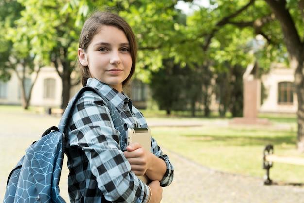 Tiro medio de la vista lateral de la tableta confiada de la tenencia de la muchacha de la escuela Foto gratis