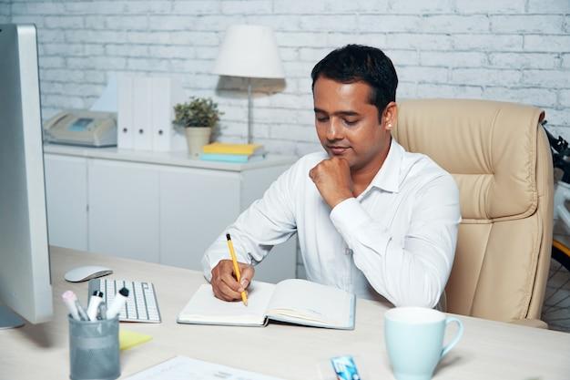 Tiro en el pecho del trabajador de cuello blanco sentado en el escritorio de la oficina y tomando notas Foto gratis